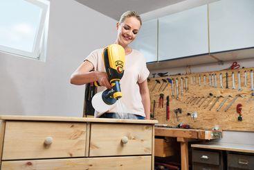 In der Werkstatt besprüht Eva Brenner die Kommode