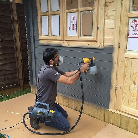 Spraying a garden house with Fence&Decking Sprayer